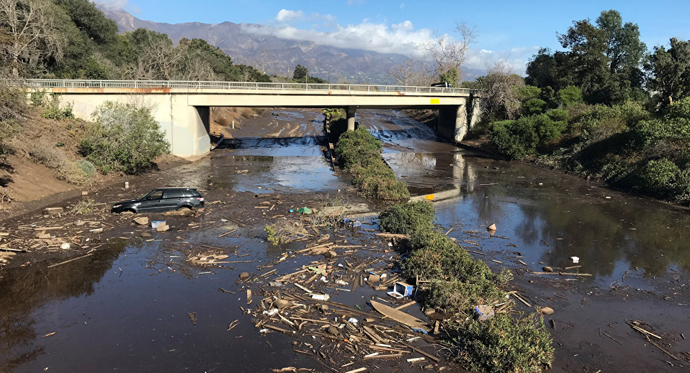 An abandoned car is seen stuck in flooded water on the 101 freeway after a mudslide in Montecito, California, U.S. January 10, 2018