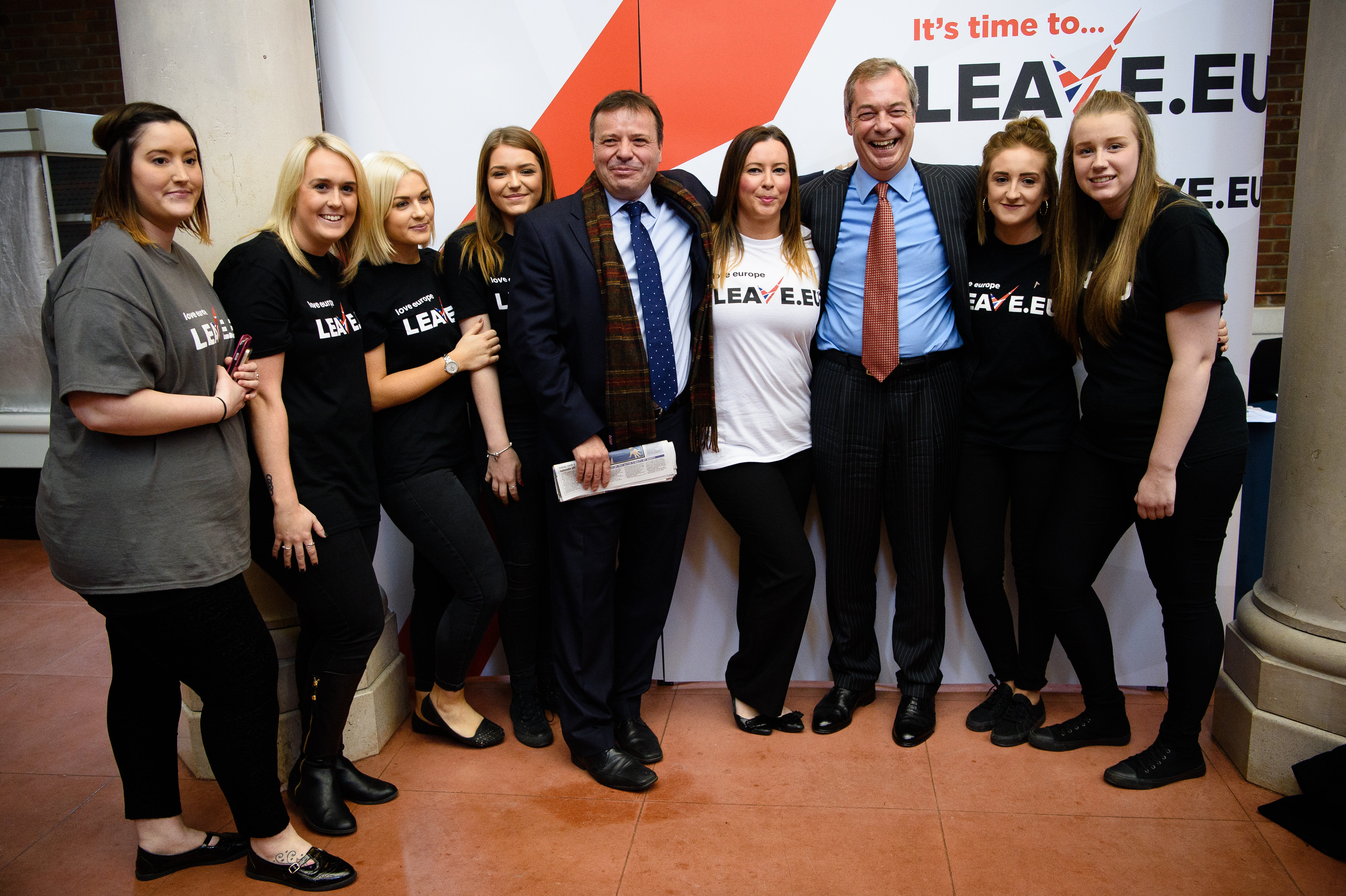 British businessman Arron Banks (C) and UKIP leader Nigel Farage (3R) pose with volunteers after a press briefing by the Leave.EU campaign group in central London on November 18, 2015