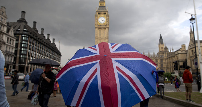 A pedestrian shelters from the rain beneath a Union flag themed umbrella as they walk near the Big Ben clock face and the Elizabeth Tower at the Houses of Parliament in central London. (File)