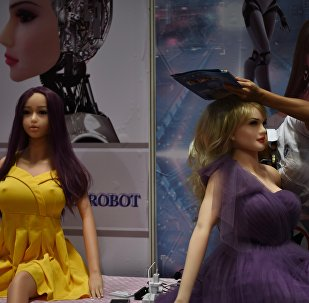 An exhibitor (R) adjusts an adult sex toy doll at her stall during the Asia Adult Expo in Hong Kong. (File)