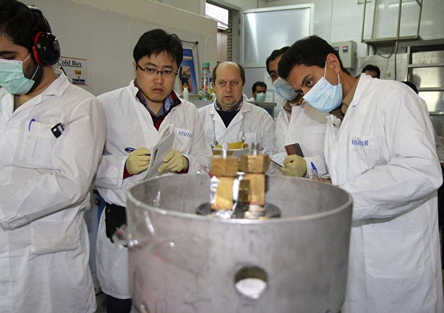 Unidentified IAEA inspectors and Iranian technicians are on hand to cut the connections between the twin cascades for 20 percent uranium enrichment at Natanz facility, some 200 miles (322 kilometers) south of the Iranian capital Tehran, Jan. 20, 2014