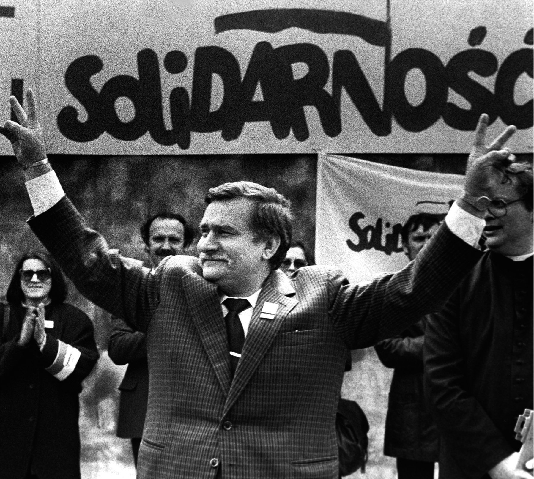 Polish President and Solidarity founding leader Lech Walesa shows v-sign in front of Solidarity poster during his presidential campaign in Plock in this May 7, 1989 file photo