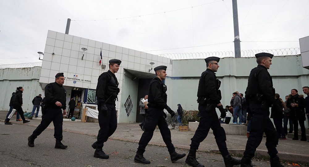 Riot police officers walk by Borgo prison on January 22, 2018 on the French Mediterranean Island of Corsica, as striking prison guards block its access as part of a nationwide movement to call for better safety and wages