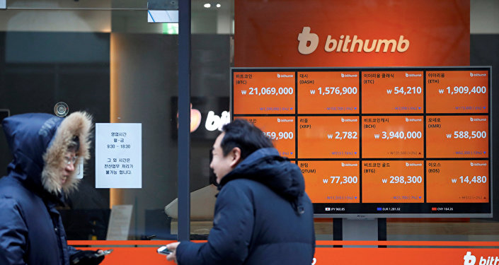 Men talk in front of an electric board showing exchange rates of various cryptocurrencies at Bithumb cryptocurrencies exchange in Seoul, South Korea, January 11, 2018