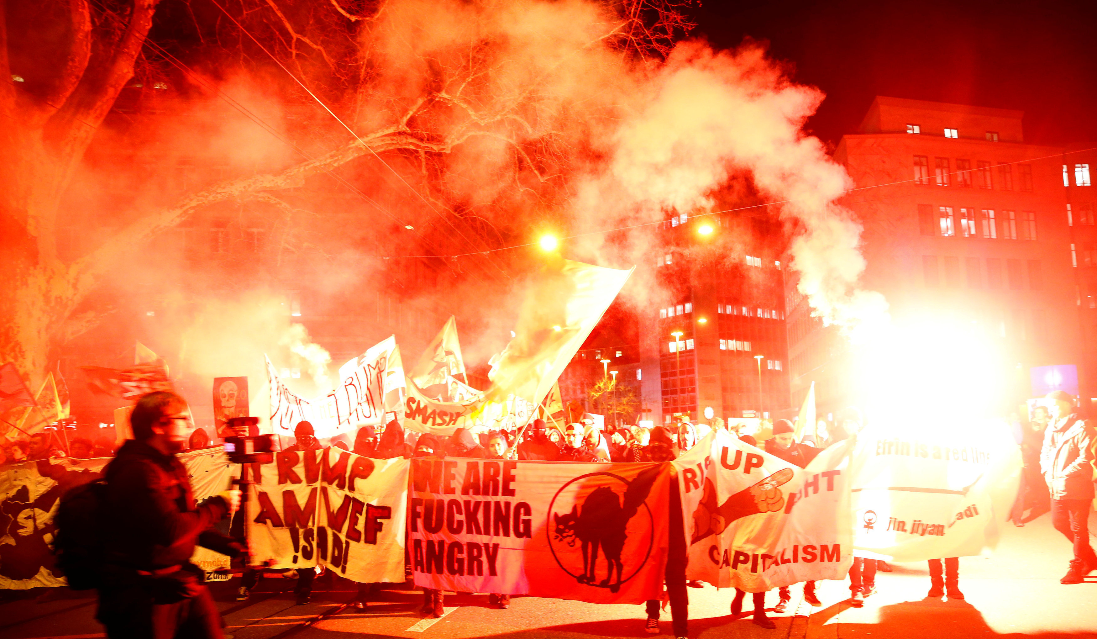 Protesters with banners light flares during a demonstration against U.S. President Trump in Zurich