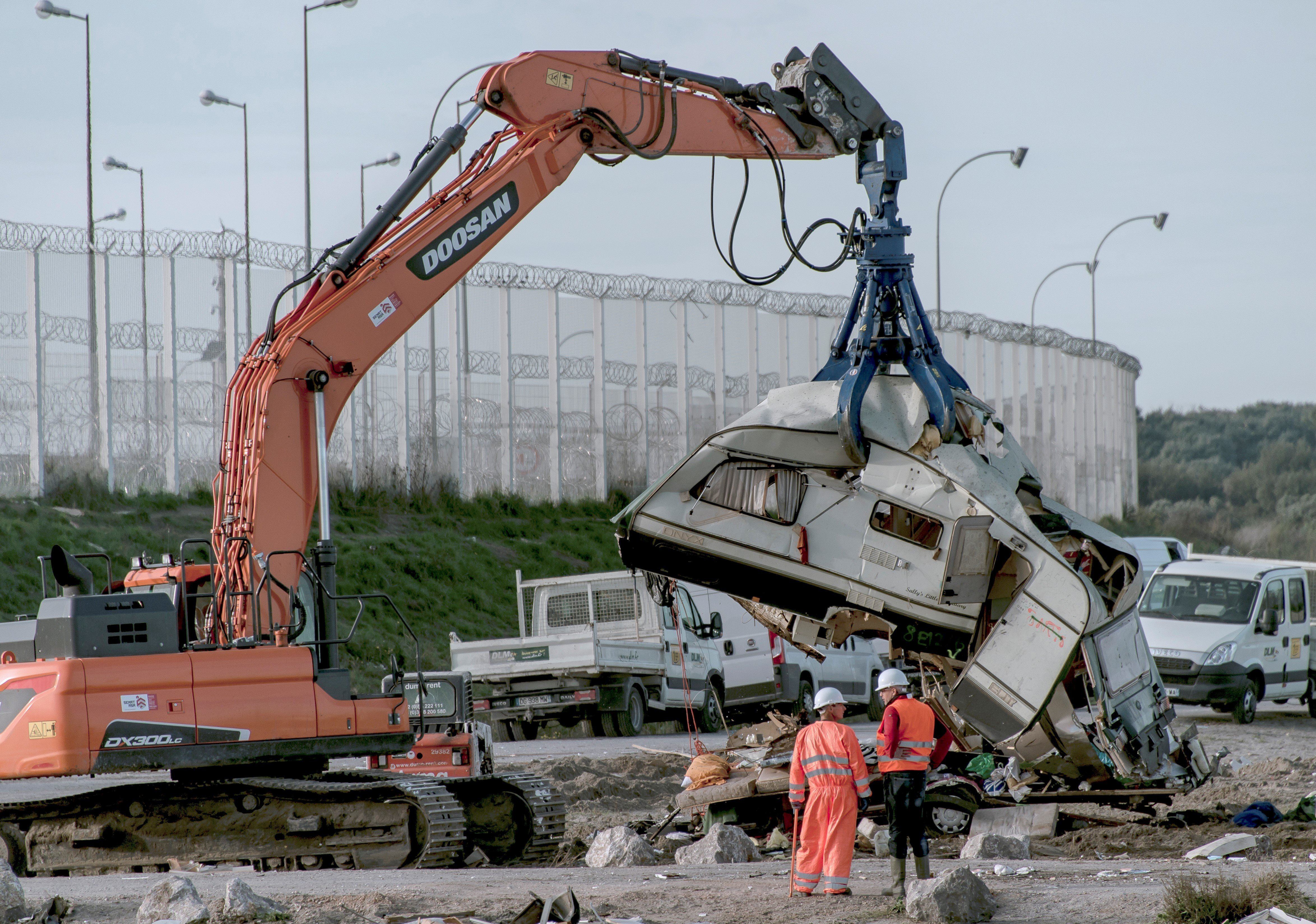 Workers watch as a crane destroys a caravan, once used as a makeshift shelter, at the site of the 'Jungle' migrant camp, on October 31, 2016 in Calais, northern France, as a massive operation to clear the settlement nears completion