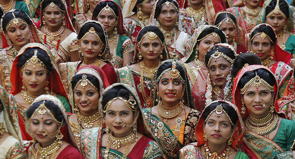 Indian brides pose for photograph before a mass wedding in Surat, India, Sunday, Dec. 24, 2017