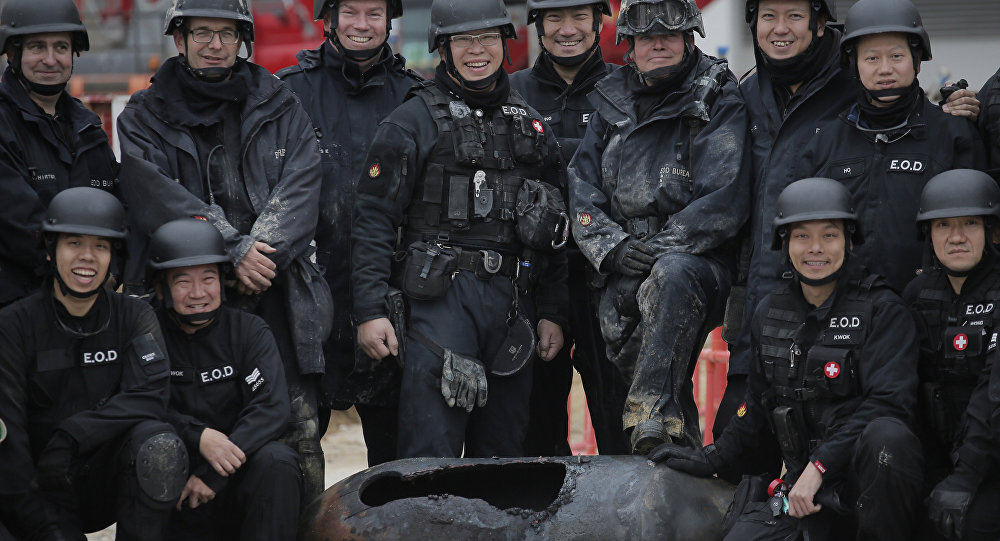 Police officers from explosive ordinance disposal pose with a deactivated bomb for a photo at the scene in the Wan Chai district of Hong Kong, Thursday, Feb.1, 2018. Hong Kong police worked overnight to neutralize the large unexploded wartime bomb after it was unearthed on Wednesday during construction work in the Asian financial center.
