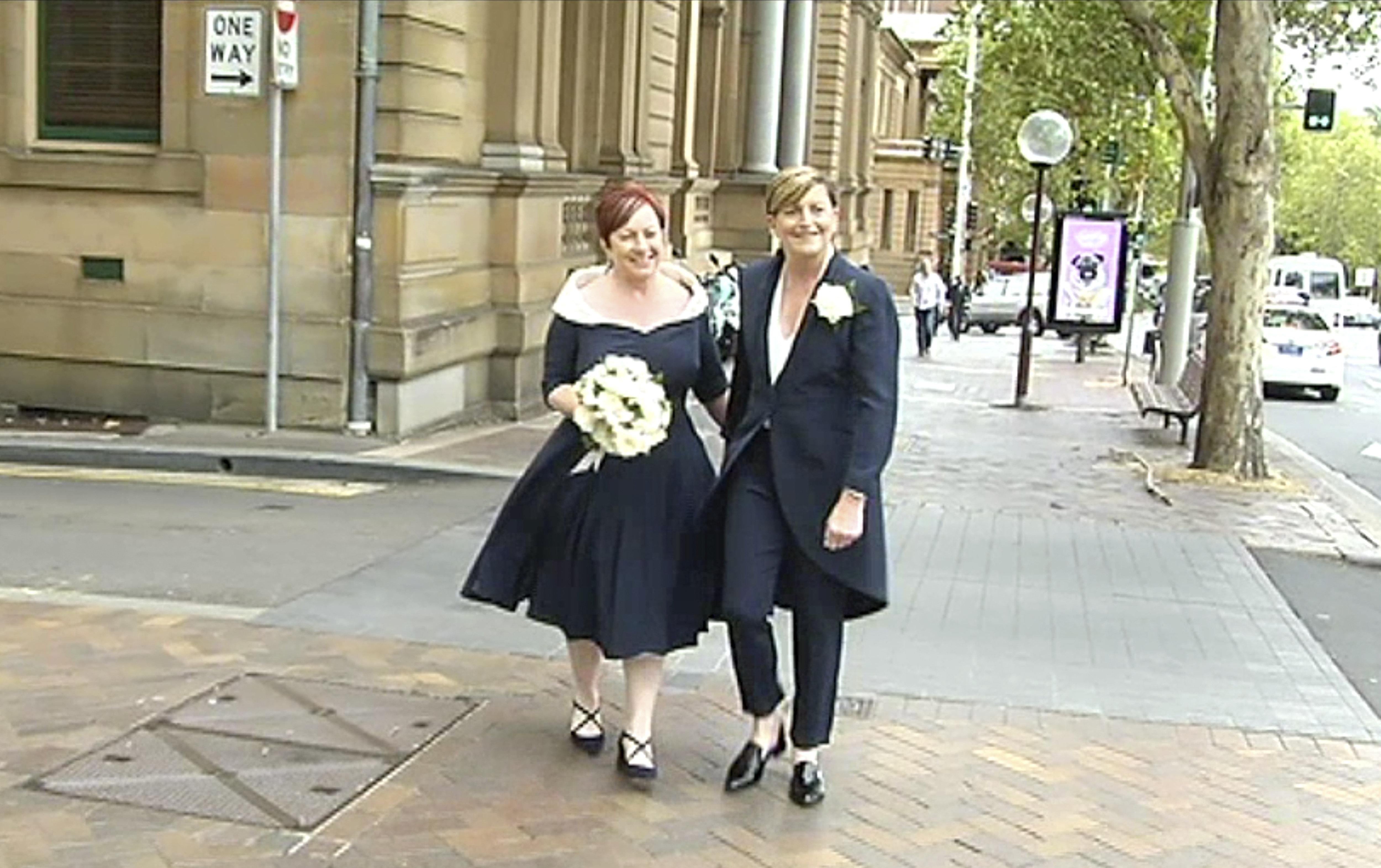 In this image made from Australia Broadcasting Corporation video, Christine Forster, right, sister of former Australian Prime Minister Tony Abbott, walks with her partner Virginia Edwards, Feb. 2, 2018, in Sydney, Australia