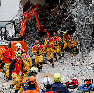 Rescuers run out of a hotel during an aftershock after an earthquake hit Hualien, Taiwan February 7, 2018