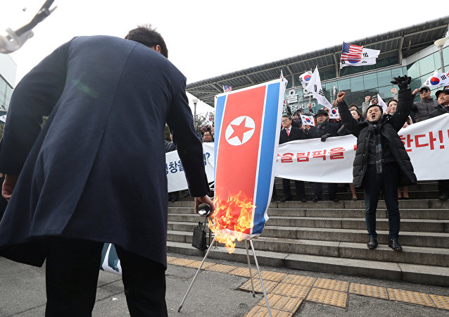 A member of a South Korean conservative civic group burns a North Korean national flag during a protest opposing North Korea's participation in the 2018 Pyeongchang Winter Olympics, in Seoul, South Korea, January 22, 2018