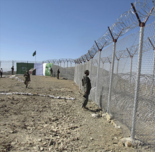 Pakistani soldiers stand guard at newly erected fence between Pakistan and Afghanistan at Angore Adda, Pakistan, Wednesday, Oct. 18, 2017