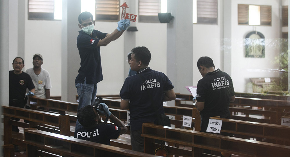 In this image shot through a glass window police investigators examine the interior of St. Lidwina Church following an attack in Sleman Yogyakarta province Indonesia Sunday Feb. 11 2018
