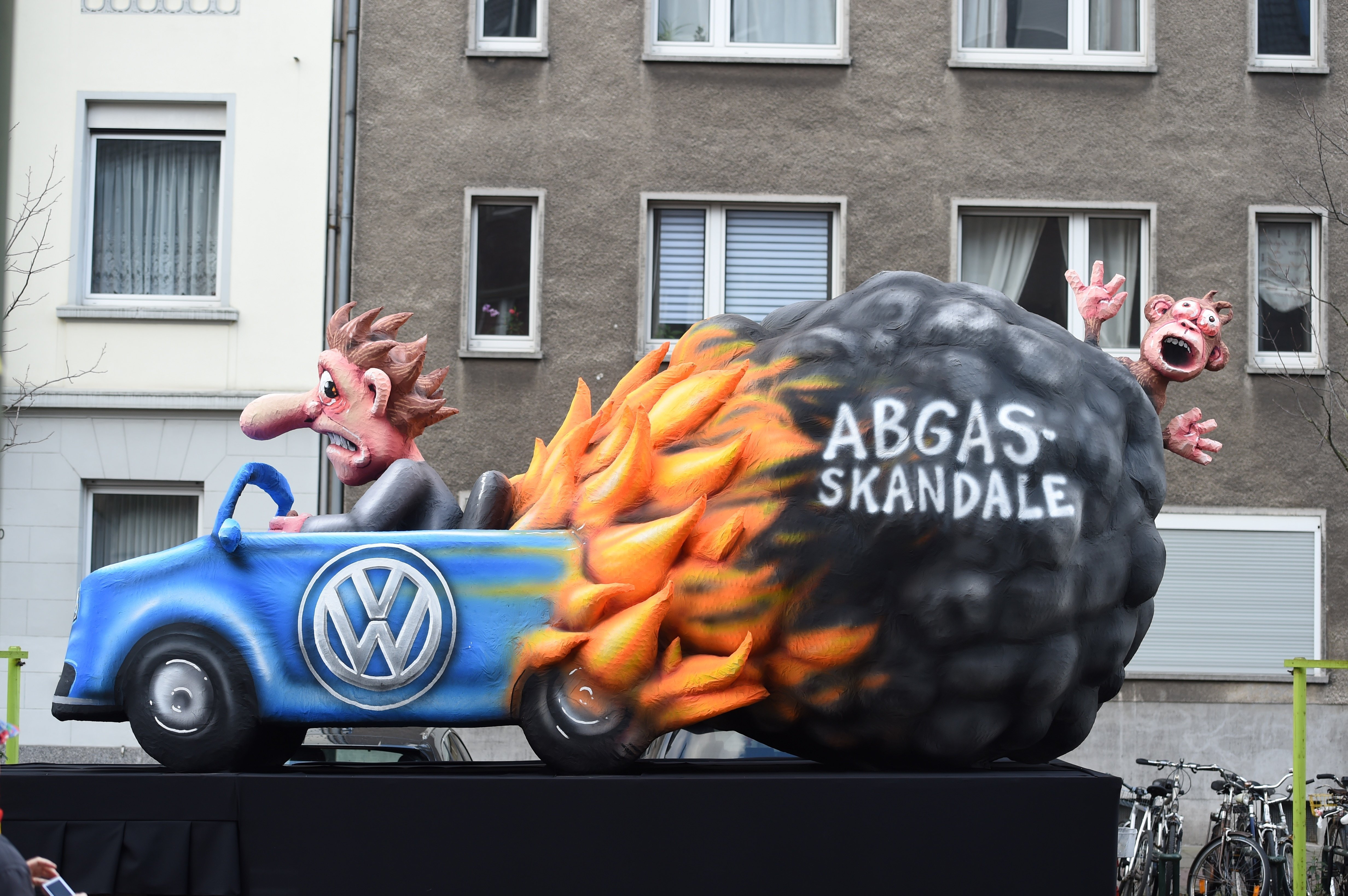 A carnival float, depicting a man driving a Wolkswagen car in flame, is pictured during a carnival parade on Rose Monday on February 12, 2018 in Duesseldorf, western Germany. The writing reads exhaust gas (R).