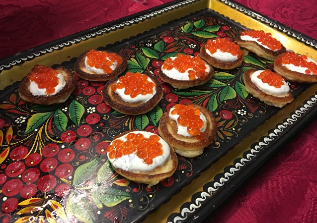 Mini pancakes served with red caviar