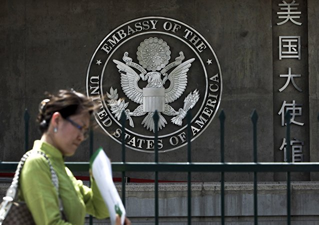 A Chinese woman checks her documents as she walks past the U.S. Embassy in Beijing Friday, May 6, 2011