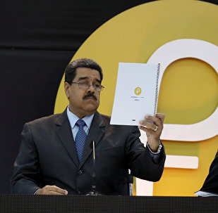 Venezuela's President Nicolas Maduro reads a document during the event launching the new Venezuelan cryptocurrency Petro in Caracas, Venezuela February 20, 2018