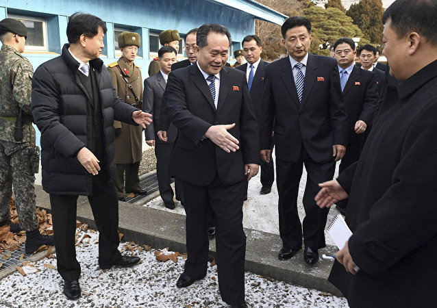 Head of North Korean delegation Ri Son Gwon, center, is greeted by South Korean officials after he crosses the border line to attend their meeting at Panmunjom in the Demilitarized Zone in Paju, South Korea, Tuesday, Jan. 9, 2018