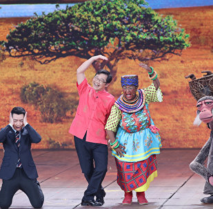 Chinese actor Lou Naiming (2-R) performs a skit on a Lunar New Year gala in Beijing, China