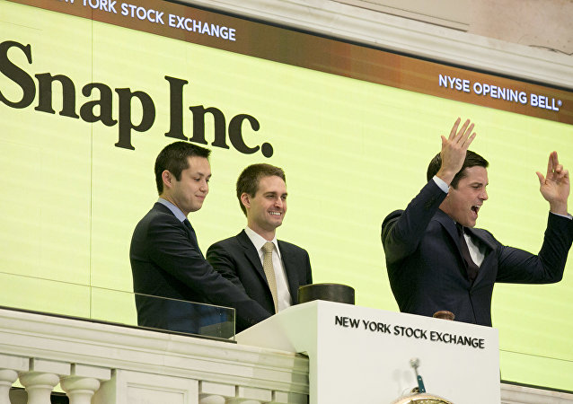 Snapchat co-founders Bobby Murphy, left, and CEO Evan Spiegel, ring the opening bell at the New York Stock Exchange while Thomas Farley, right, president of the Exchange, cheers on the crowd