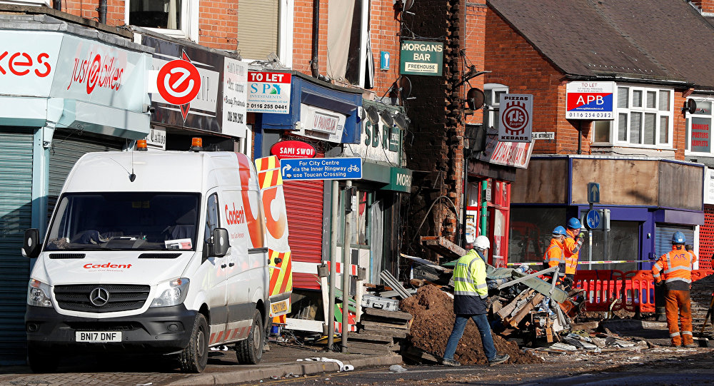 Salvage crews work at the scene of a convenience store and home that were destroyed by an explosion in Leicester, Britain