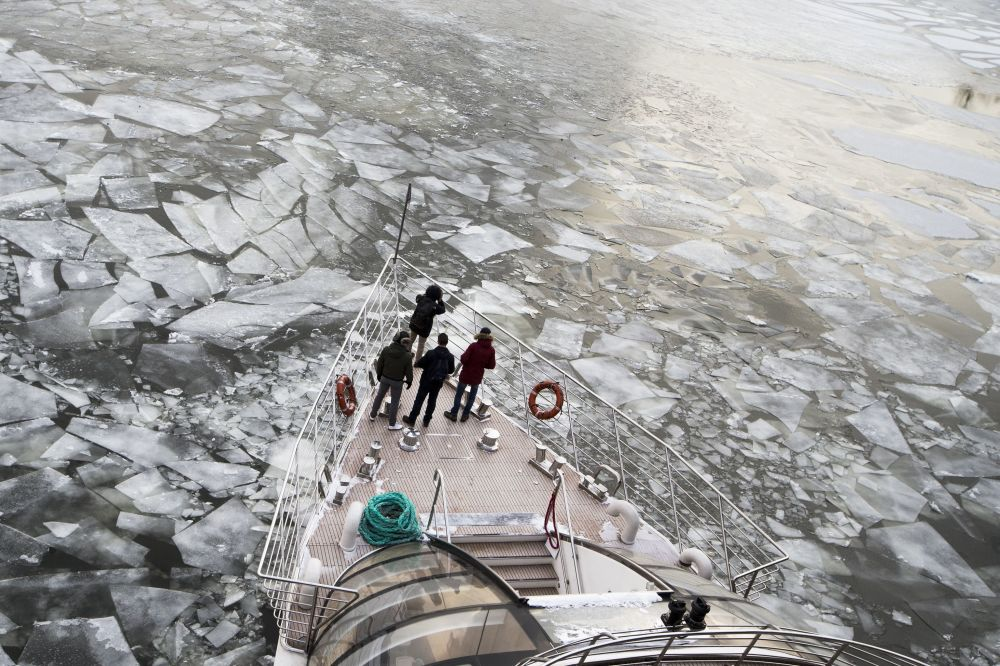 Passengers stand on a deck of a  tourist boat with restaurant aboard especially designed for winter river cruises as it breaks through the frozen Moskva River in Moscow, Russia, Monday,