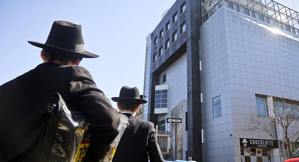 In this Thursday March 9, 2017 file photo, two young men who left a nearby synagogue watch police activity outside the Jewish Children's Museum following a bomb threat in Brooklyn borough of New York