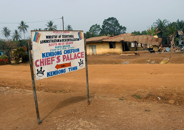 A road sign is seen in front of burned and damaged buildings in Kembong, south-west region of Cameroon December 29, 2017. Picture taken December 29, 2017