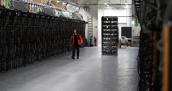 In this photo taken on Jan. 17, 2018, a worker walks along a row of computer rigs that run around the clock 'mining' bitcoin inside the Genesis Mining cryptocurrency mine in Keflavik, Iceland