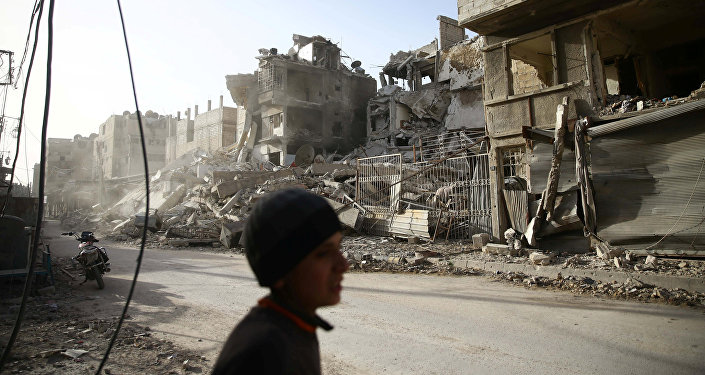 A boy walks near damaged buildings in the besieged town of Douma in eastern Ghouta in Damascus, Syria, March 1, 2018