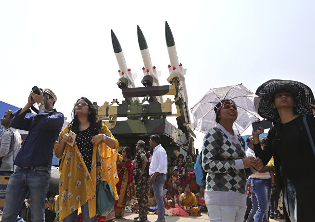 Spectators stand next to the models of Akash, surface-to-air missile, as they watch fighter aircraft perform on the fourth day of Aero India 2017 at Yelahanka air base in Bangalore, India, Friday, Feb. 17, 2017