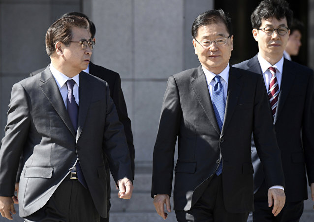 South Korea's national security director Chung Eui-yong, second right, and National Intelligence Service Chief Suh Hoon, left, talk before boarding an aircraft as they leave for Pyongyang at a military airport in Seongnam, south of Seoul, Monday, March 5, 2018.