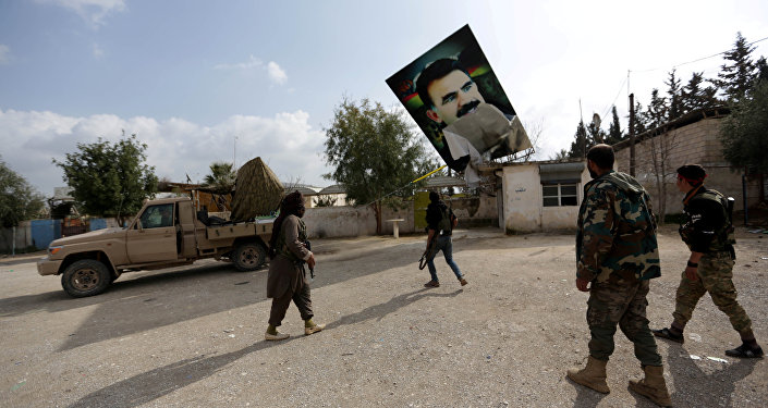 Turkish-backed Free Syrian Army fighters remove a picture of Kurdistan Workers Party (PKK) leader Abdullah Ocalan in Kafr Jana village north of Afrin, Syria March 7, 2018