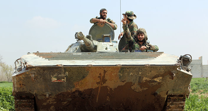 Syrian regime forces sit inside a tank in the town of Aftris, west of the rebel-held town of Saqba, in the besieged Eastern Ghouta region on the outskirts of the capital Damascus, on March 10, 2018
