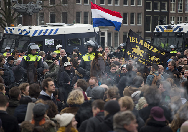 (File) A flag reads Islamists Not Welcome as mounted Dutch riot police separates pro and anti Pegida demonstrators during a rally against islamisation in Amsterdam, Netherlands, Saturday, Feb. 6, 2016