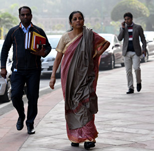 Indian defence minister Nirmala Sitharaman (C) walks after arriving for the winter session of Parliament in New Delhi on December 15, 2017
