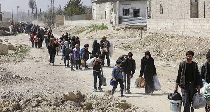 Syrians civilians evacuated from the Eastern Ghouta enclave pass with belongings through the regime-controlled corridor opened by government forces in Hawsh al-Ashaari east of the enclave town of Hamouria on the outskirts of the capital Damascus on March