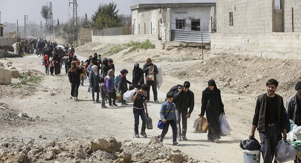 Syrians civilians evacuated from the Eastern Ghouta enclave pass with belongings through the regime-controlled corridor opened by government forces in Hawsh al-Ashaari, east of the enclave town of Hamouria on the outskirts of the capital Damascus on March 15, 2018