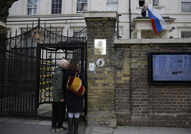 Two people wait to get into the Russian Embassy as a man works to untangle the national flag flown from the Russian Embassy, after it became entangled on its staff at the embassy in London, Wednesday, March 14, 2018