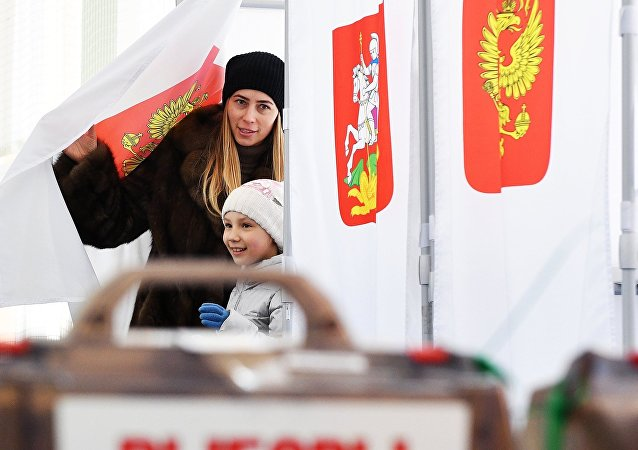 A woman with a child during the voting at the Russian presidential elections at polling station No. 13-06 in Moscow