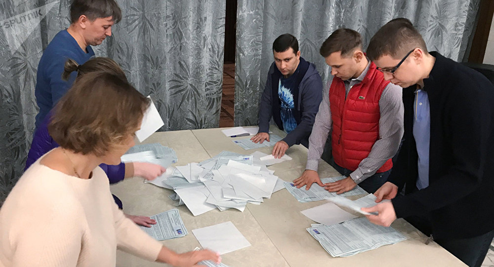 The staff of the polling station on the territory of the Russian Embassy in Damascus count votes after early voting in the Russian presidential election