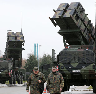 Soldiers of the Air Defence Missile Squadron 2 walk past Patriot missile launchers in the background in Bad Suelze, northern Germany on December 4, 2012