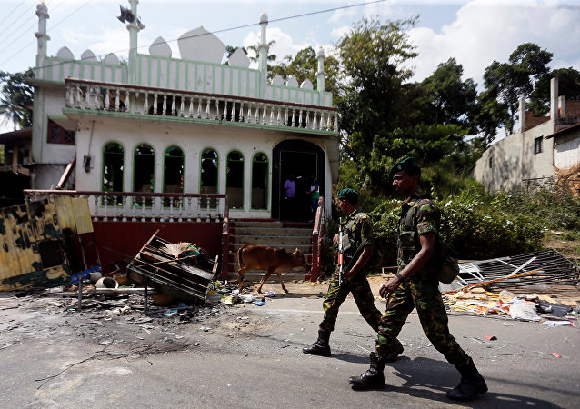 Sri Lanka's Special Task Force soldiers walk past a damaged mosque after a clash between two communities in Digana central district of Kandy, Sri Lanka March 8, 2018