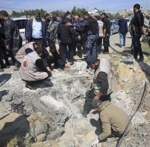 Hamas security services personnel inspect the site of a Tuesday explosion that occurred as the convoy of Palestinian Prime Minister Rami Hamdallah entered Gaza through the Erez crossing with Israel, on the main road in Beit Hanoun, Gaza Strip, Tuesday, March 13, 2018