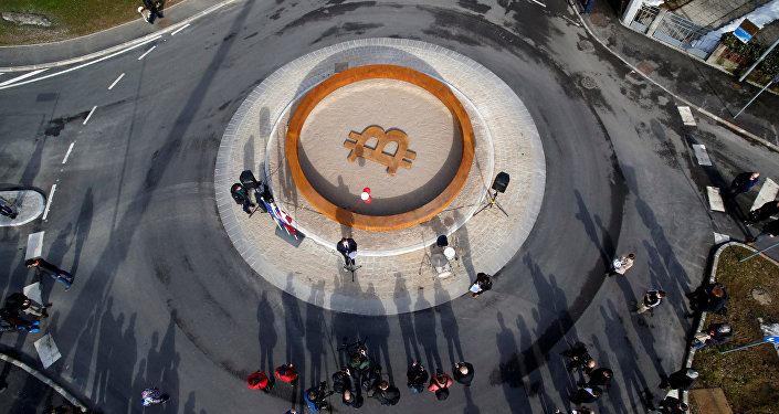 People attend the opening ceremony of world's first public Bitcoin monument, placed at a roundabout connecting two roads at the city centre in Kranj, Slovenia, March 13, 2018