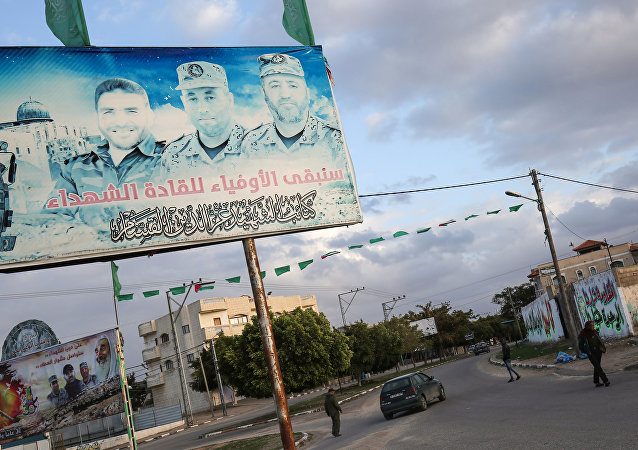 A Palestinian vehicle drives through a roundabout past a billboard bearing the portraits of Mohammed Abu Shamala (R) and Raed al-Attar (C), commanders of Hamas' armed wing al-Qassam Brigades, in Rafah in the southern Gaza Strip on January 19, 2018