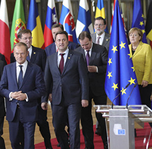 European Council President Donald Tusk, front center, and European Commission President Jean-Claude Juncker, front left, lead EU leaders to a group photo at an EU summit at the Europa building in Brussels on Thursday, Dec. 14, 2017