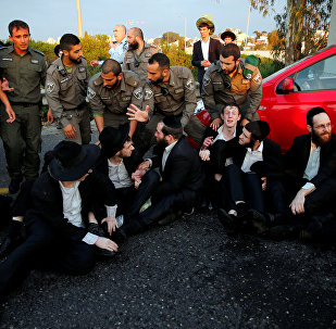 An Israeli ultra-Orthodox Jew block a main road in Israel before security forces evacuate them during a protest against the detention of a member of his community who refuses to serve in the Israeli army, in Bnei Brak, Israel
