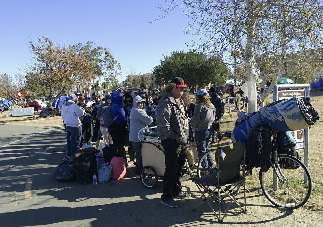 Homeless people line up in preparation to move from their homeless camp site along a riverbed in Anaheim, CA