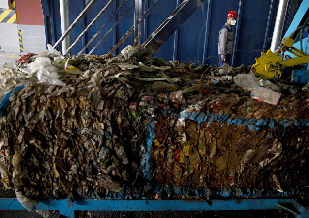 A worker walks past garbage being processed at the Majialou Garbage Transfer Station in Beijing, China, Thursday, March 30, 2017